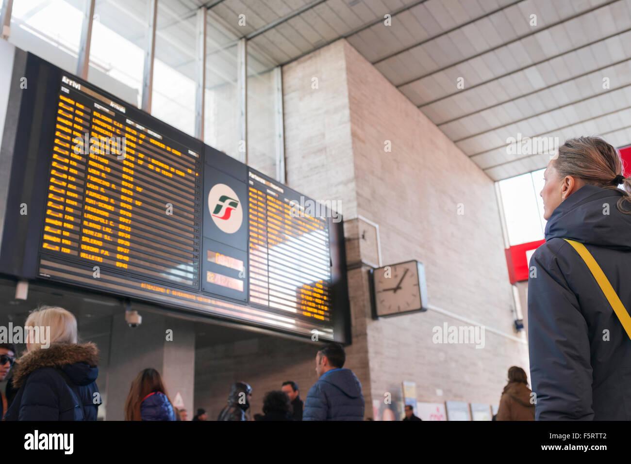 Italy, Lazio, Rome, Senior woman looking at arrival departure board - Stock Image
