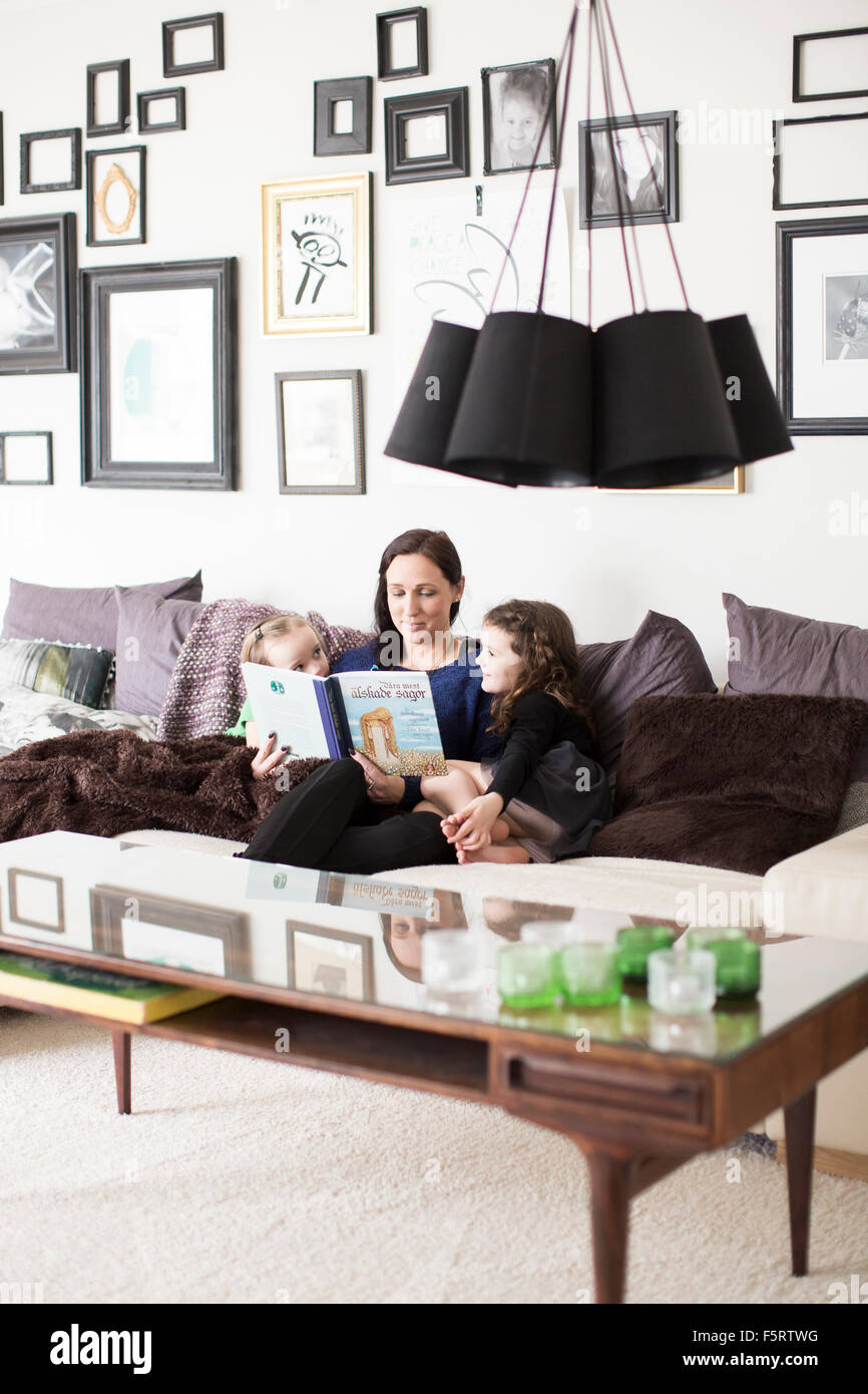Sweden, Mom reading to her daughters (6-7) - Stock Image