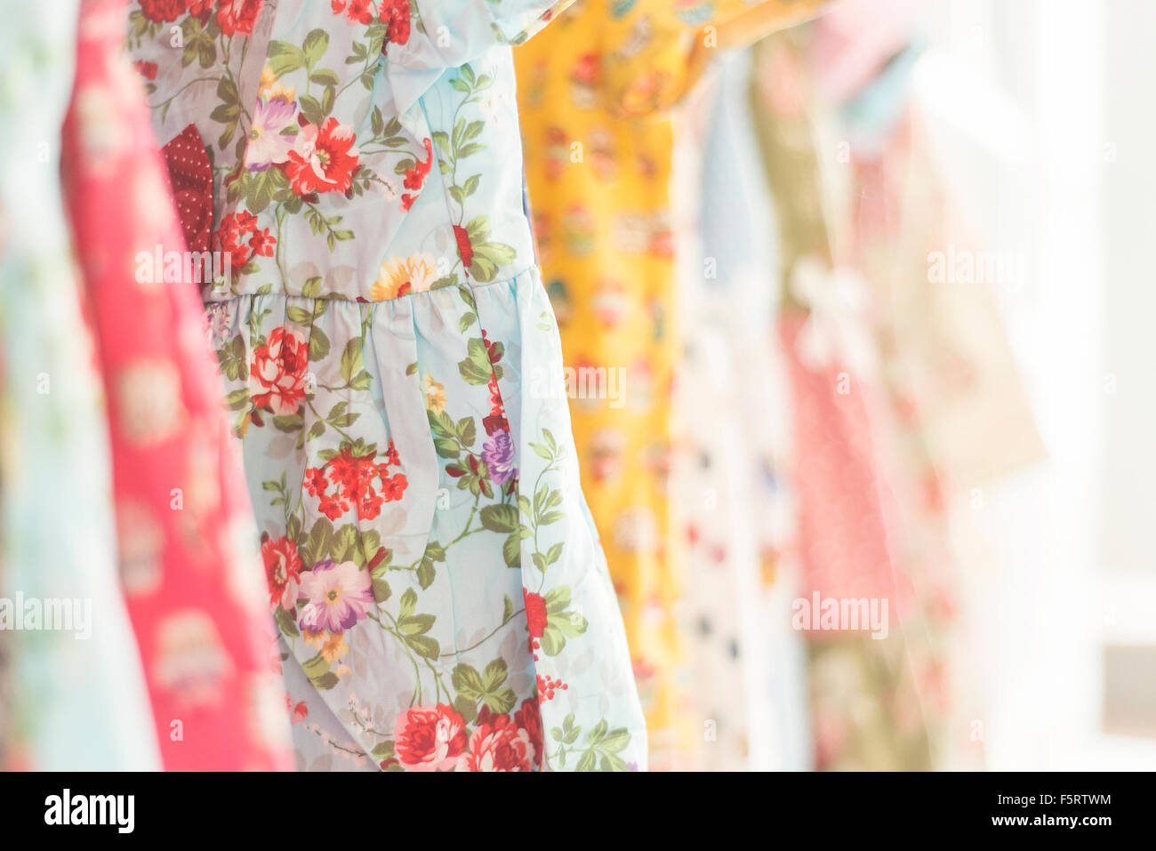floral pattern young girl dresses in children wear fashion shop - Stock Image