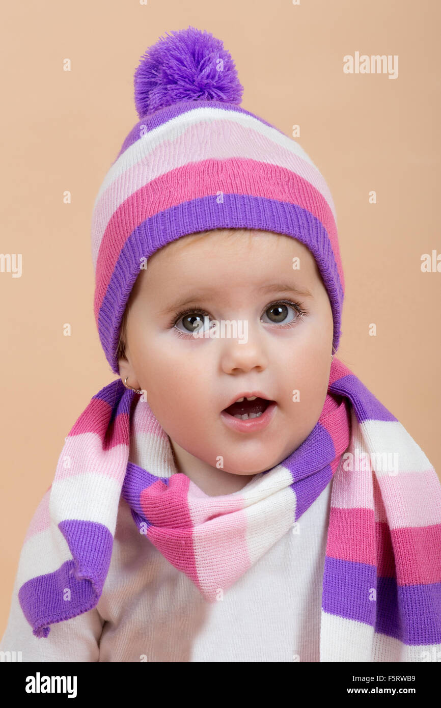 1078915a6f52 portrait of young cute baby with winter cap and scarf on beige Stock ...