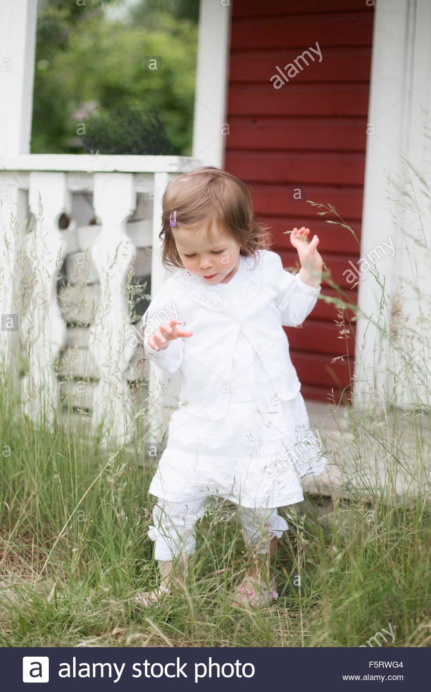 Sweden, Vasterbotten, Hemavan, Girl (2-3) exploring backyard - Stock Image