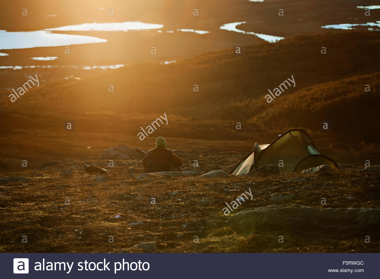 Sweden, Vasterbotten, Hemavan, Man camping at sunset - Stock Image
