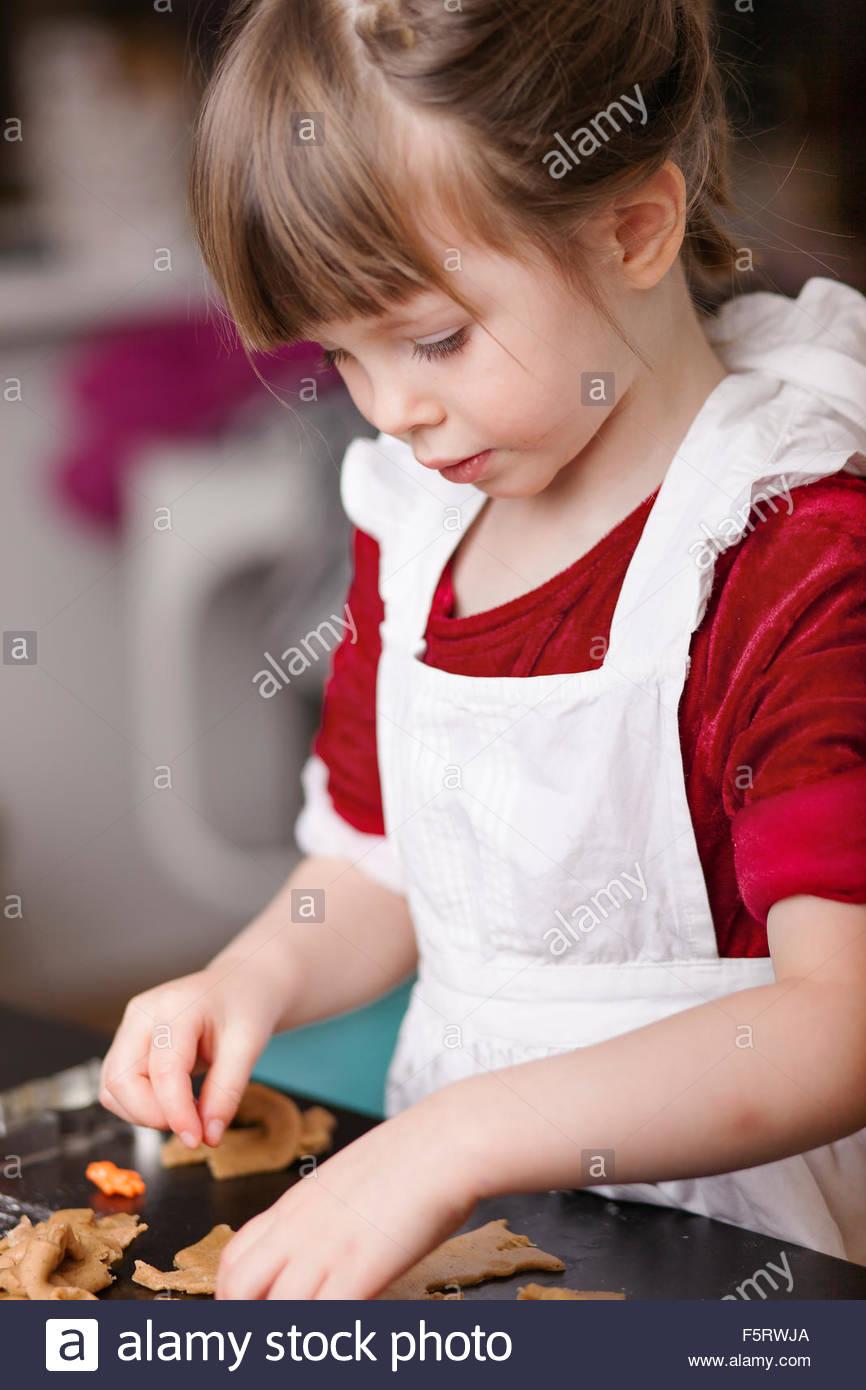Sweden, Girl (4-5) making gingerbread cookies - Stock Image
