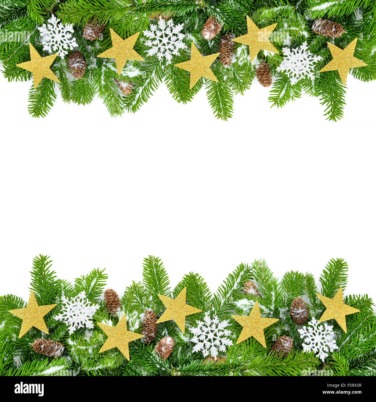 Frame of fresh fir twigs with stars, snow and cones, studio isolated on white background - Stock Image