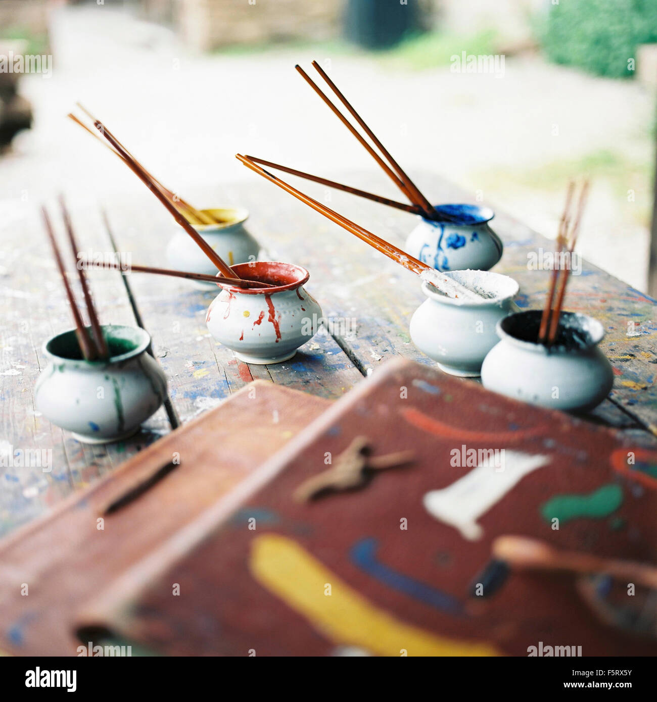 Sweden, Oland, Paintbrushes in small bowls - Stock Image