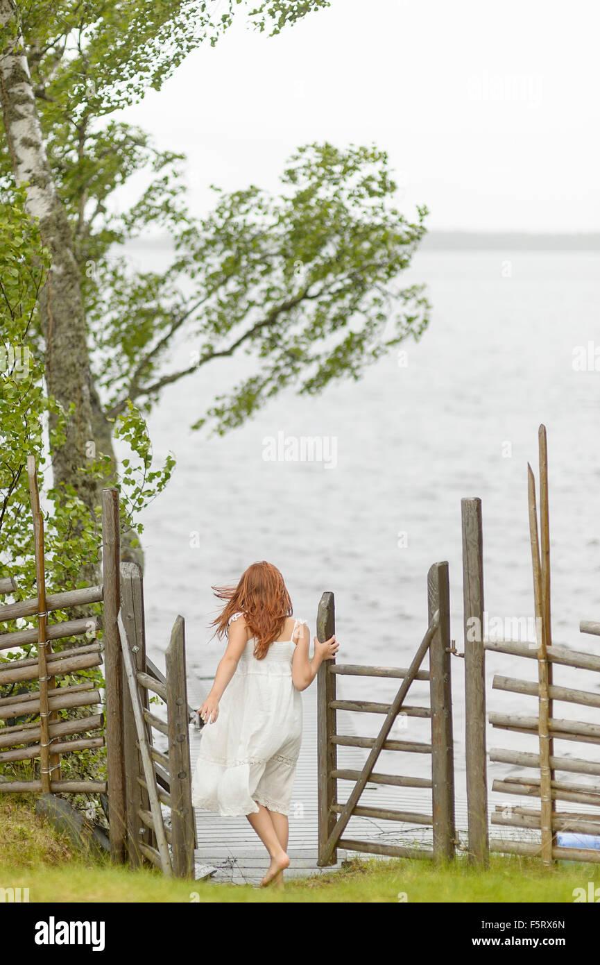 Sweden, Vastmanland, Bergslagen, Hallefors, Sangshyttan, Girl (8-9) walking towards lake - Stock Image
