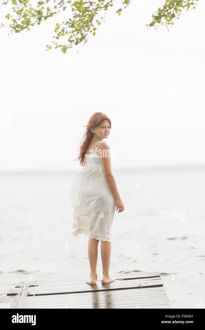 Sweden, Vastmanland, Bergslagen, Hallefors, Sangshyttan, Girl (8-9) standing on jetty by lake - Stock Image