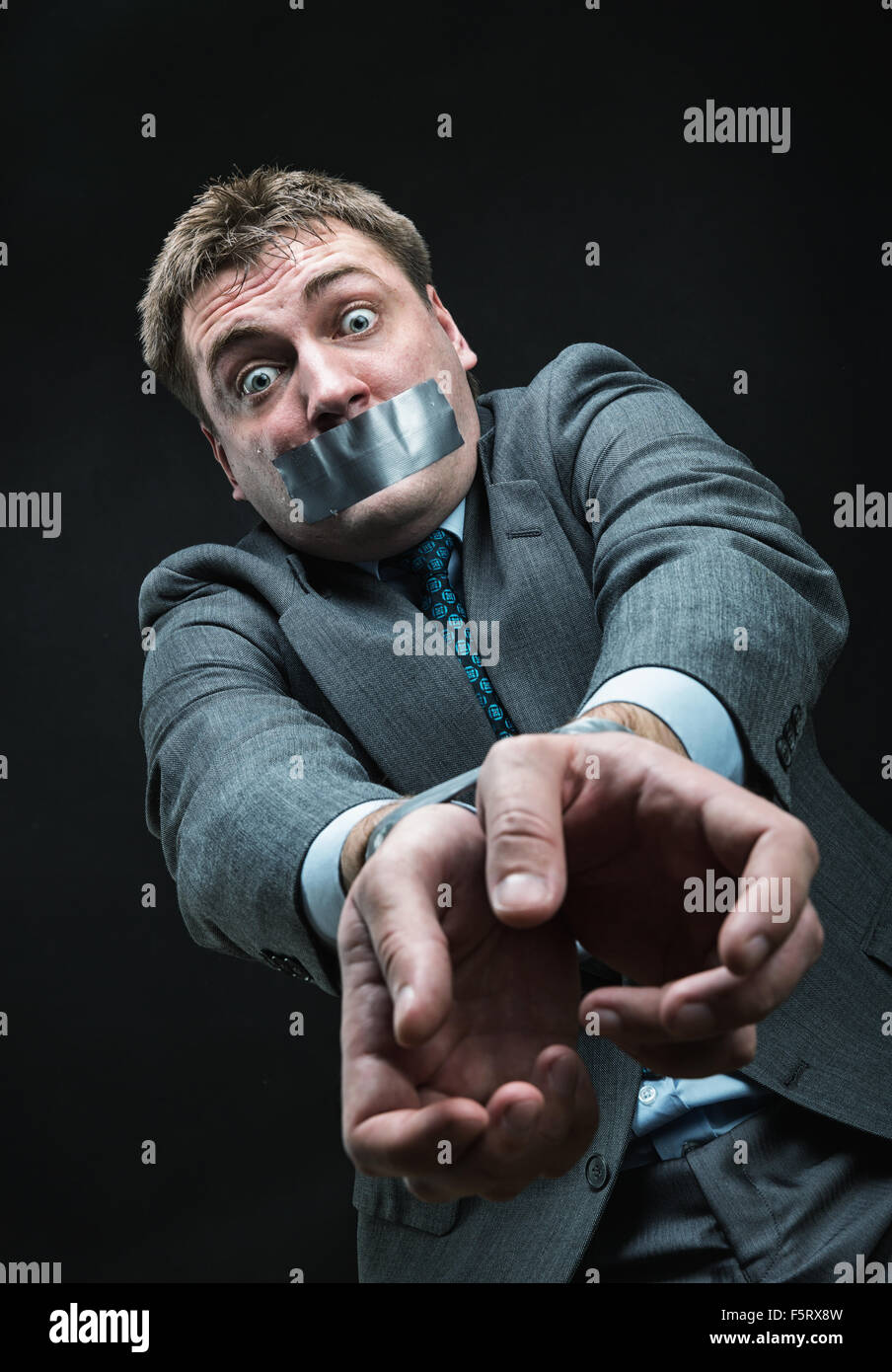 Man with mouth and hands  covered by masking tape, studio shoot - Stock Image