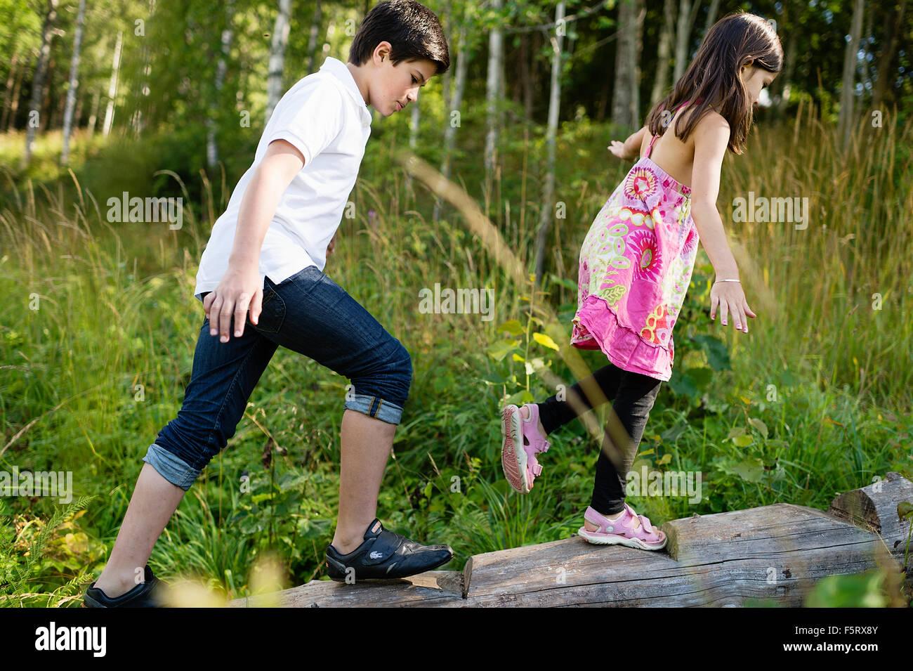 Sweden, Vastmanland, Bergslagen, Boy (10-11) and girl (6-7) walking along log - Stock Image