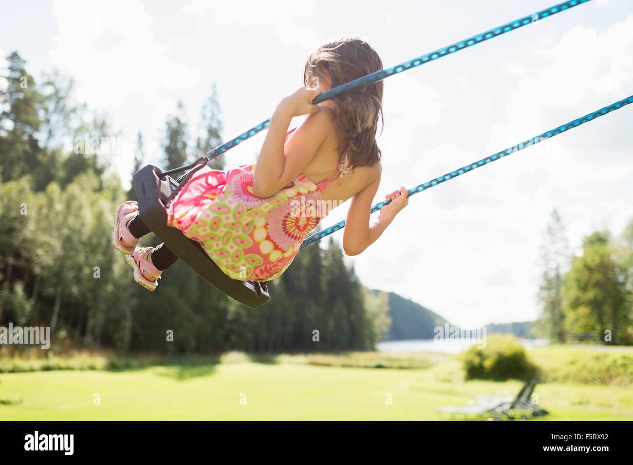 Sweden, Vastmanland, Bergslagen, Girl (6-7) on swing - Stock Image