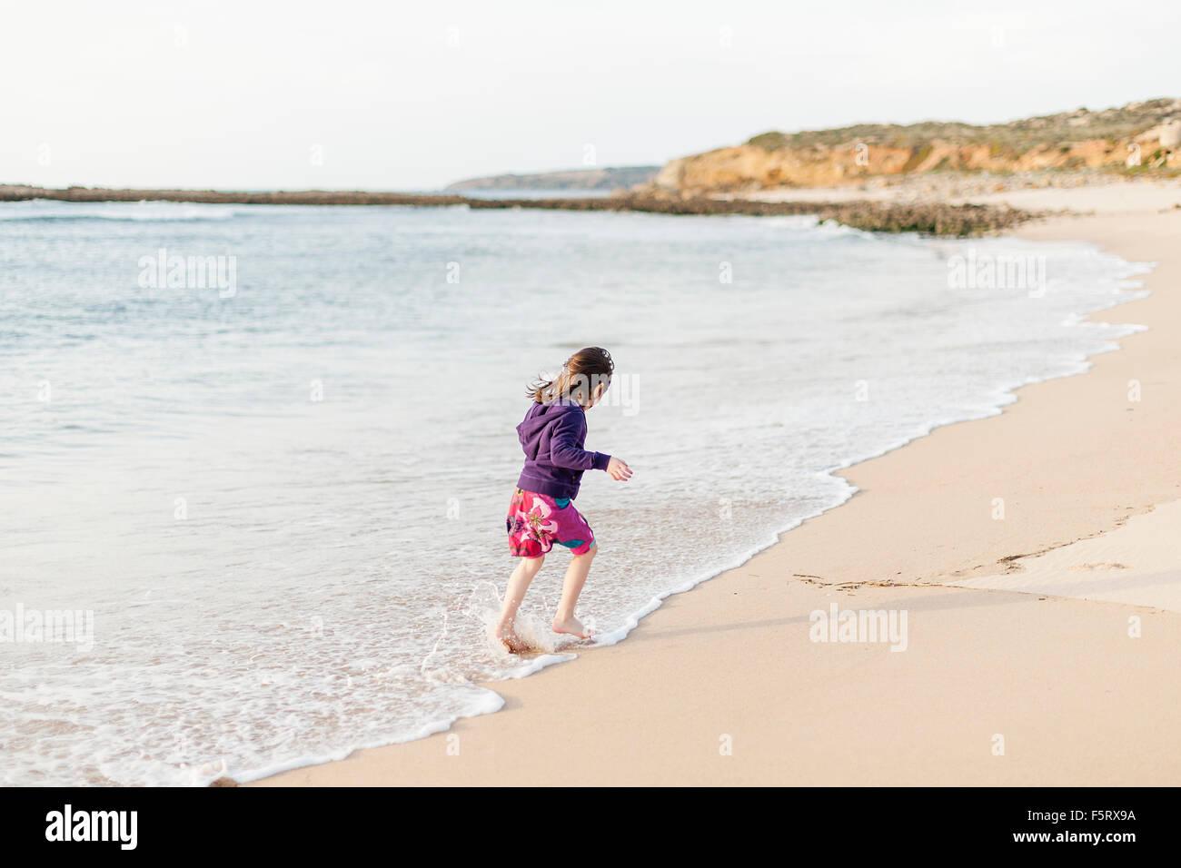 Portugal, Alentejo, Vila Nova de Milfontes, Girl (4-5) running in surf - Stock Image