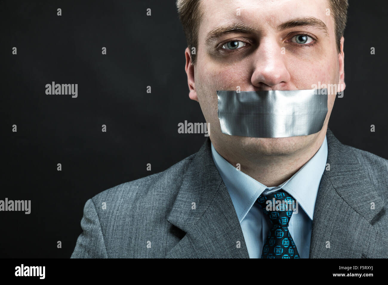 Man with mouth covered by masking tape preventing speech, studio shoot - Stock Image