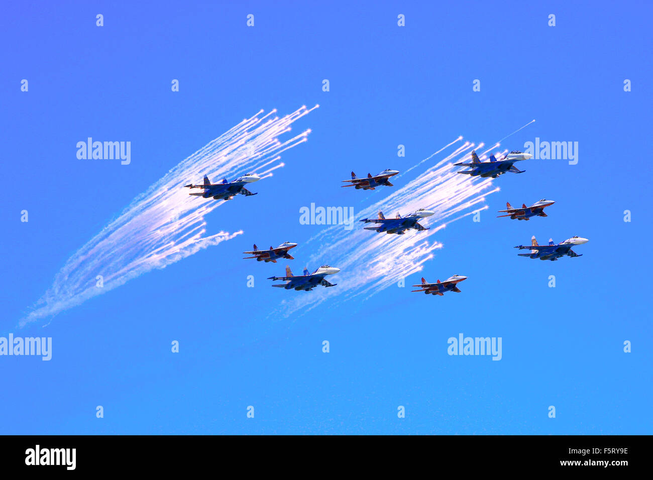 Russian MIG-29 and Su-27 fighter jets flying in front of decoy countermeasure flares over the Red Square in Moscow, - Stock Image