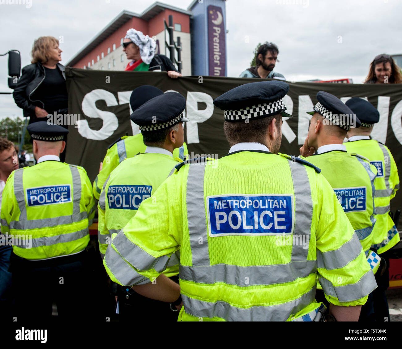 Police remove a vicar from a blockade during a protest against the DSEI, one of the world's largest arms fairs. Stock Photo