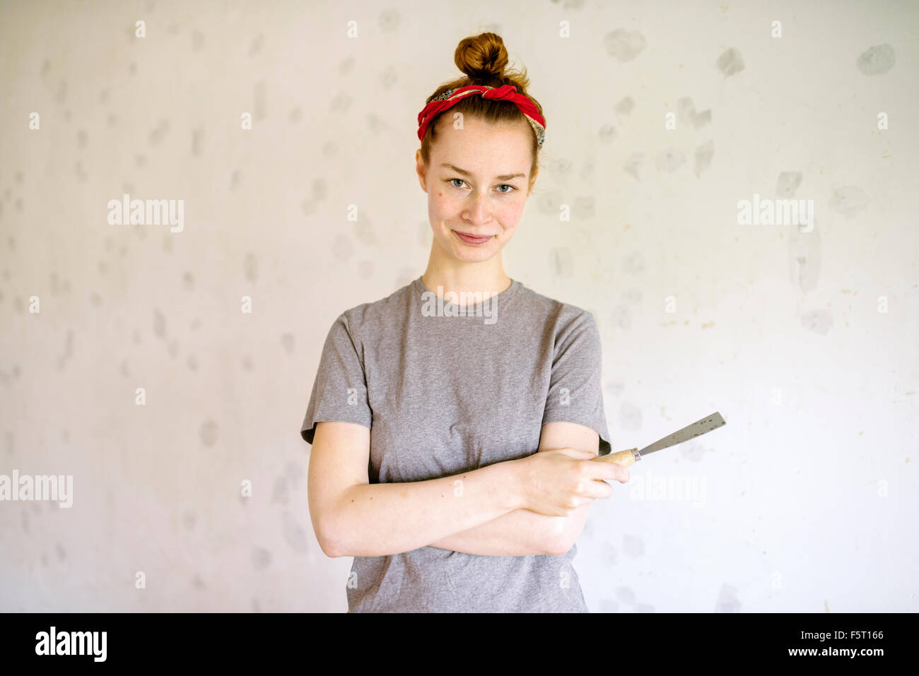 Sweden, Portrait of young woman holding hand tool - Stock Image