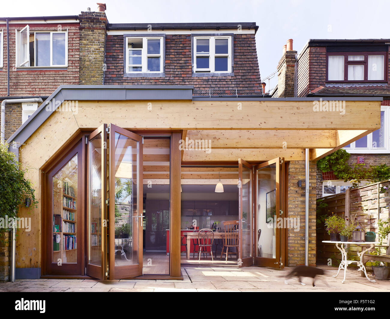 Timber frame of extension with concertina doors viewed from garden terrace. Wendell Rd London United Kingdom. Architect Tate & Timber frame of extension with concertina doors viewed from garden ...