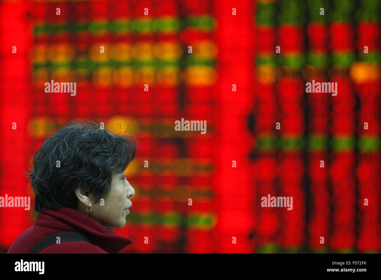An investor watchs electric board in a stock market in Huaibei, Anhui province, east China on 9th November 2015. - Stock Image
