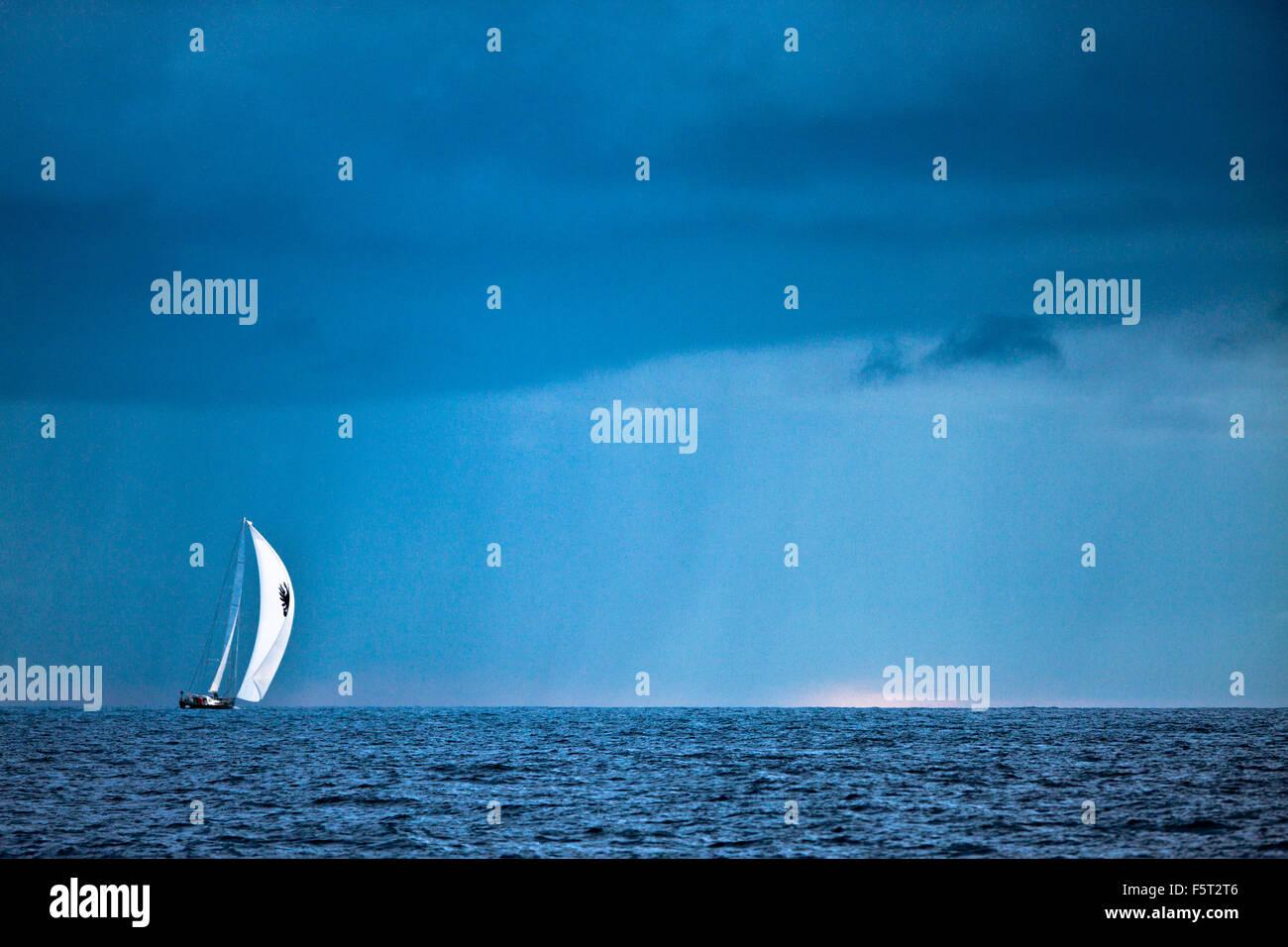 Antigua and Barbuda, Antigua, Sailboat in sea and rain cloud - Stock Image
