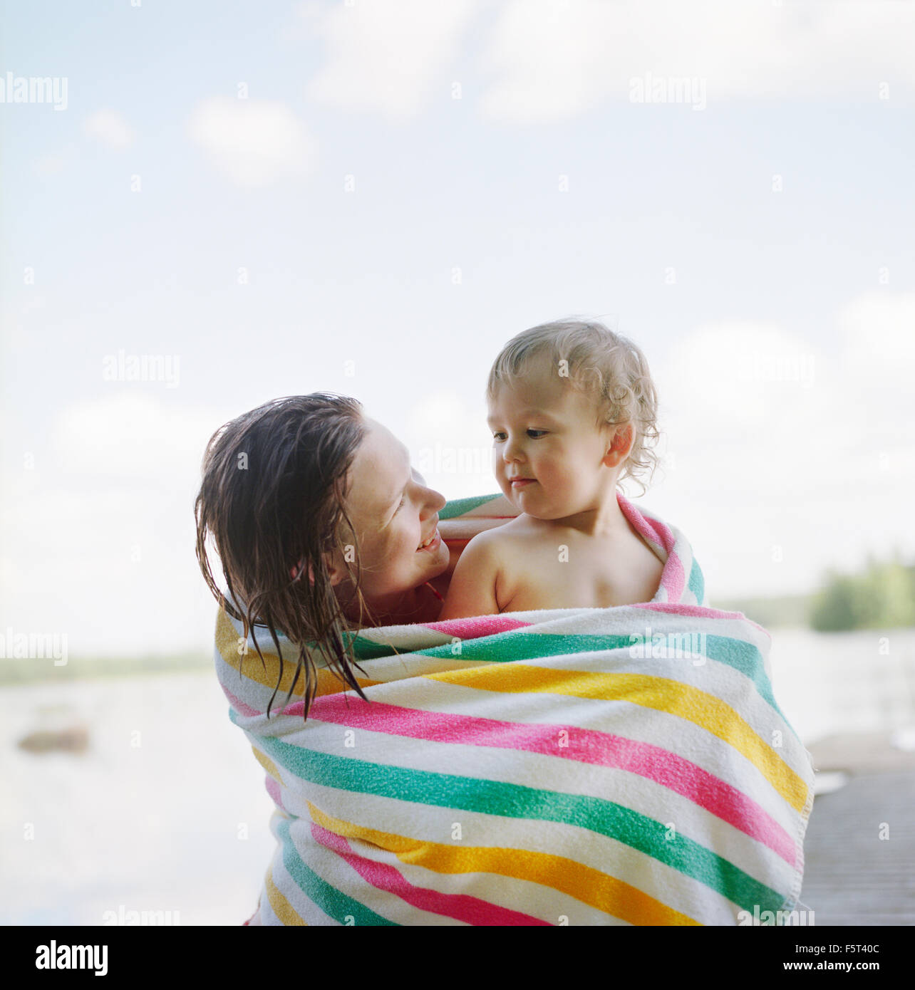 Finland, Uusimaa, Lapinjarvi, Mother and daughter (2-3) wrapped in towel - Stock Image
