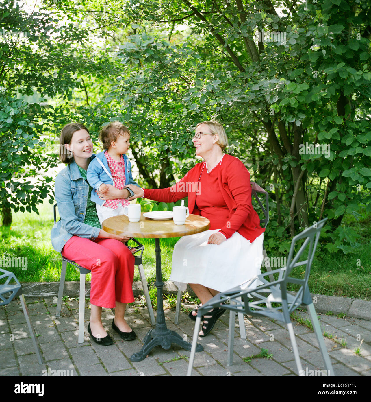 Finland, Helsinki, Uusimaa, Portrait of mother, grandmother and child (2-3) in sidewalk cafe - Stock Image