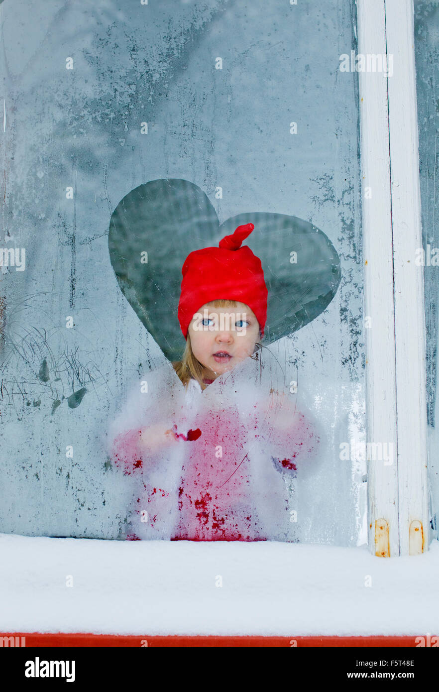 Girl (2-3) looking through frosted window - Stock Image