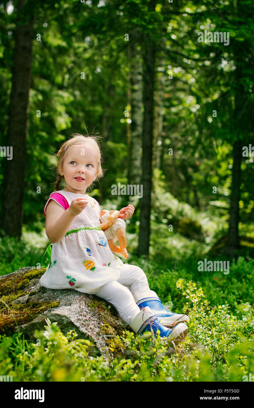 Finland, Paijat-Hame, Girl (2-3) playing with doll in forest - Stock Image