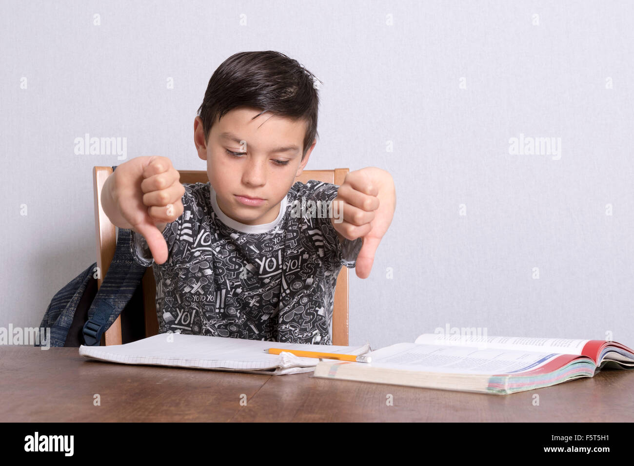 Young boy giving thumbs down over homework - Stock Image
