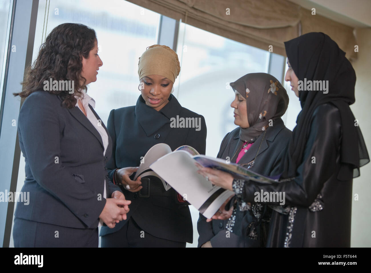 Muslim Women students discussing chatting in office environment - Stock Image