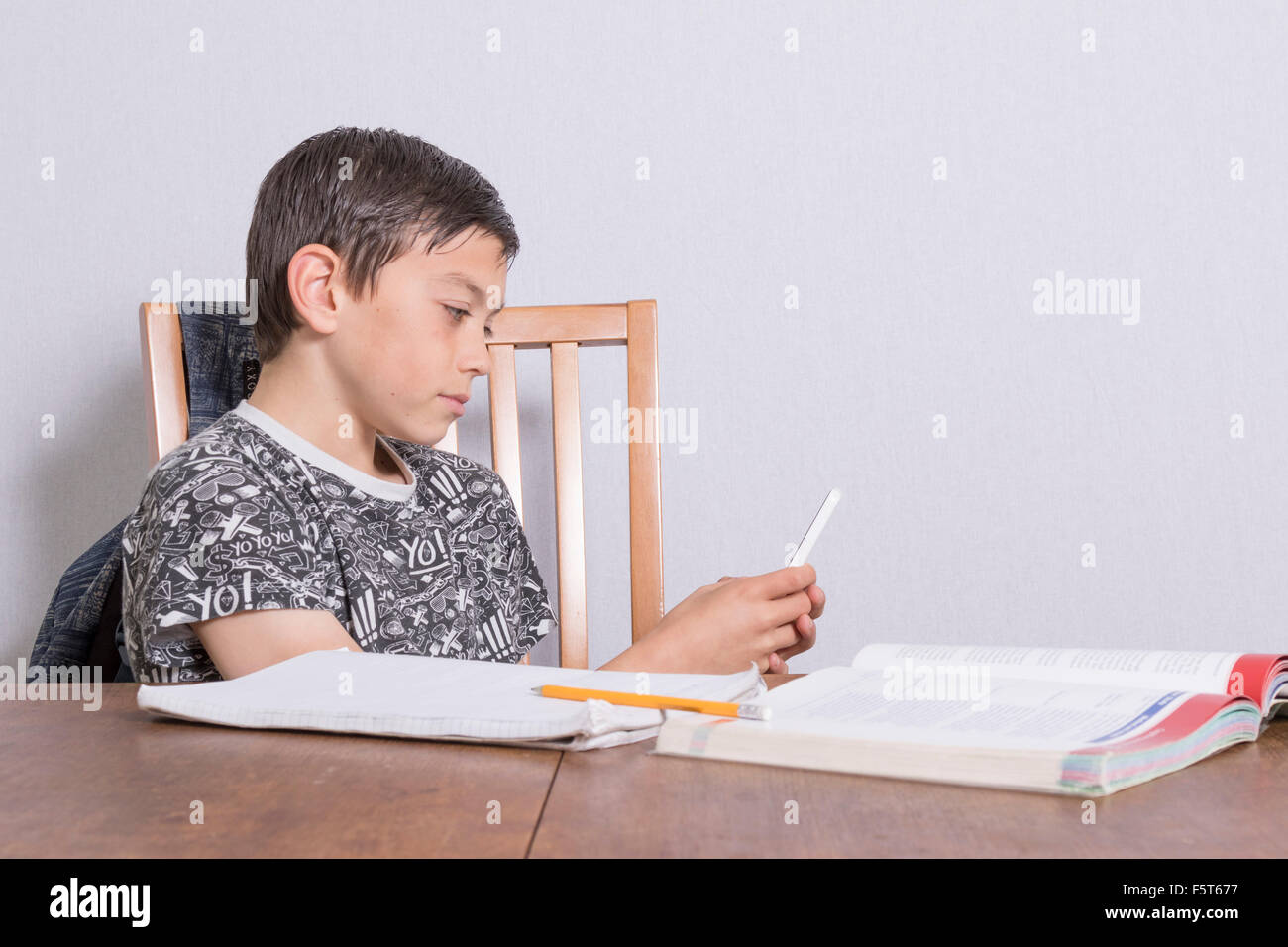 Pre-teen boy distracted by his phone from doing his homework - Stock Image