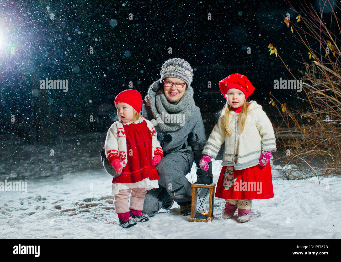Finland, Portrait of grandmother with granddaughters (12-17 months, 2-3) in backyard at night Stock Photo