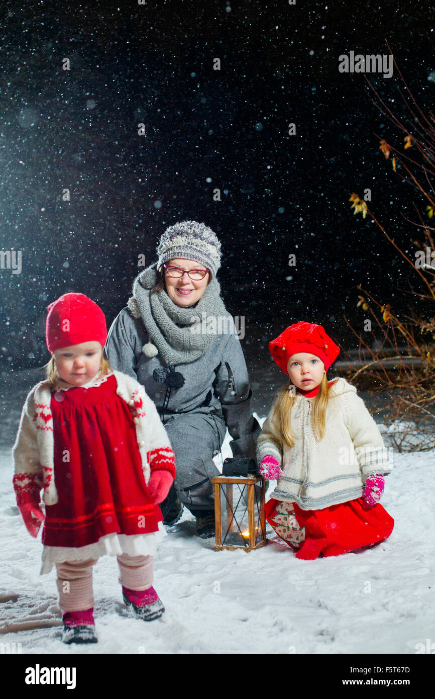 Finland, Portrait of grandmother with granddaughters (12-17 months, 2-3) in backyard at night - Stock Image
