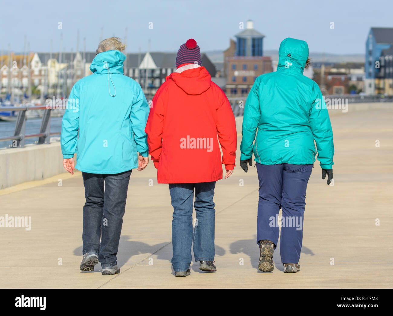 3 women wearing coats, walking away on a cold damp day in Winter in the UK. - Stock Image
