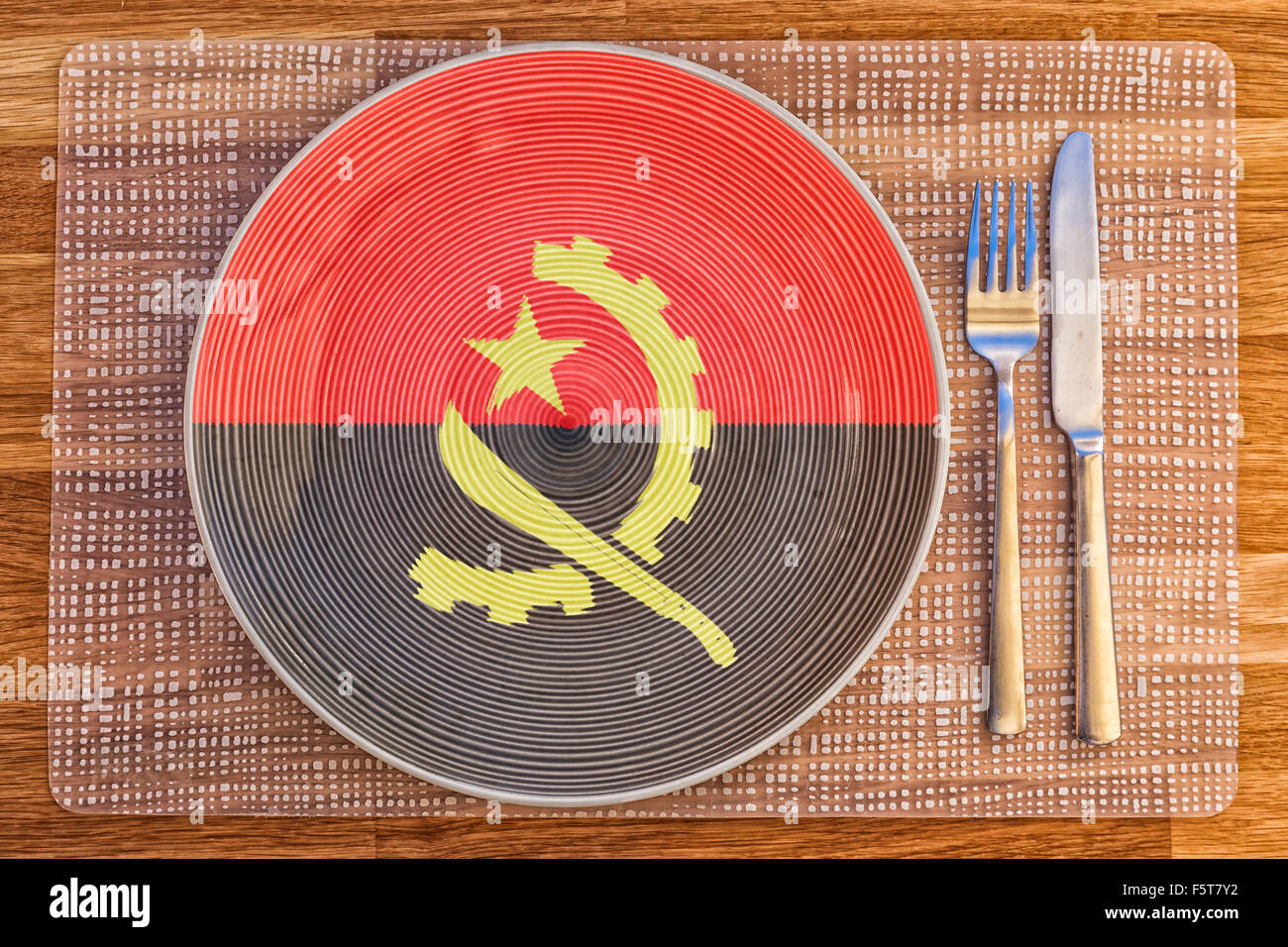 Dinner plate with the flag of Angola on it for your international food and drink concepts. - Stock Image