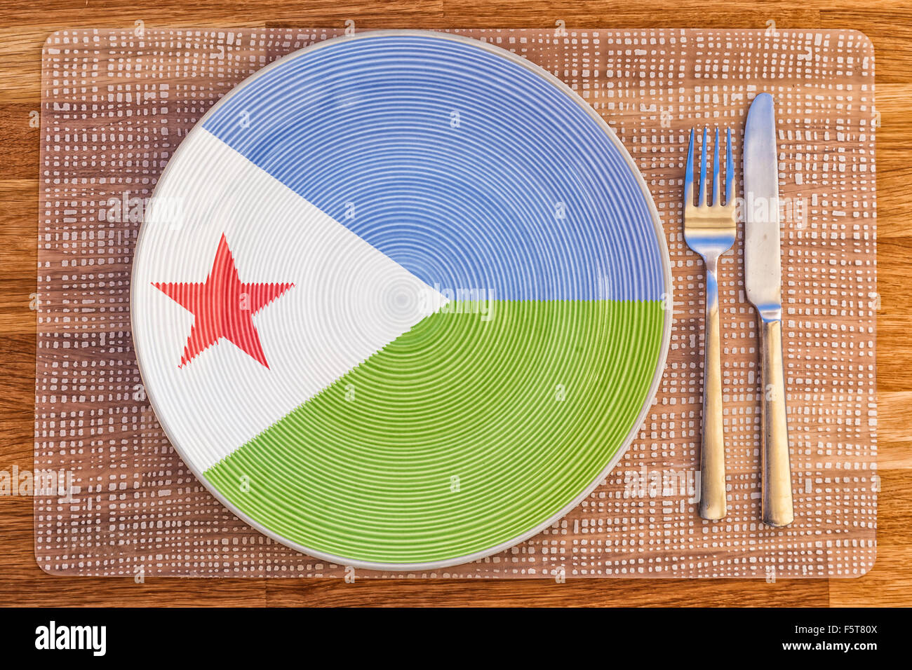 Dinner plate with the flag of Djibouti on it for your international food and drink concepts. - Stock Image