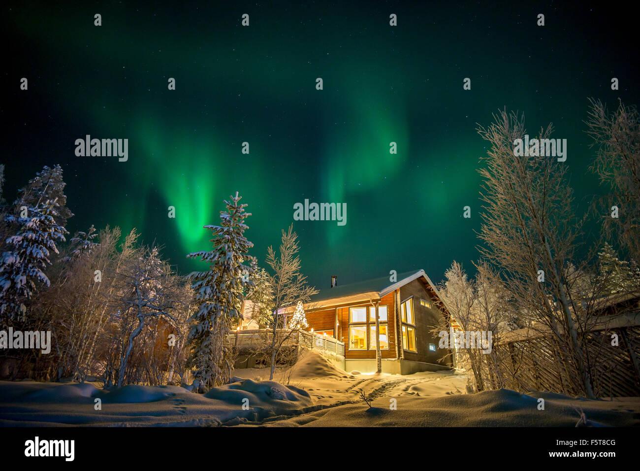 Finland, Lapland, Kittila, Levi, Aurora borealis over cottage - Stock Image