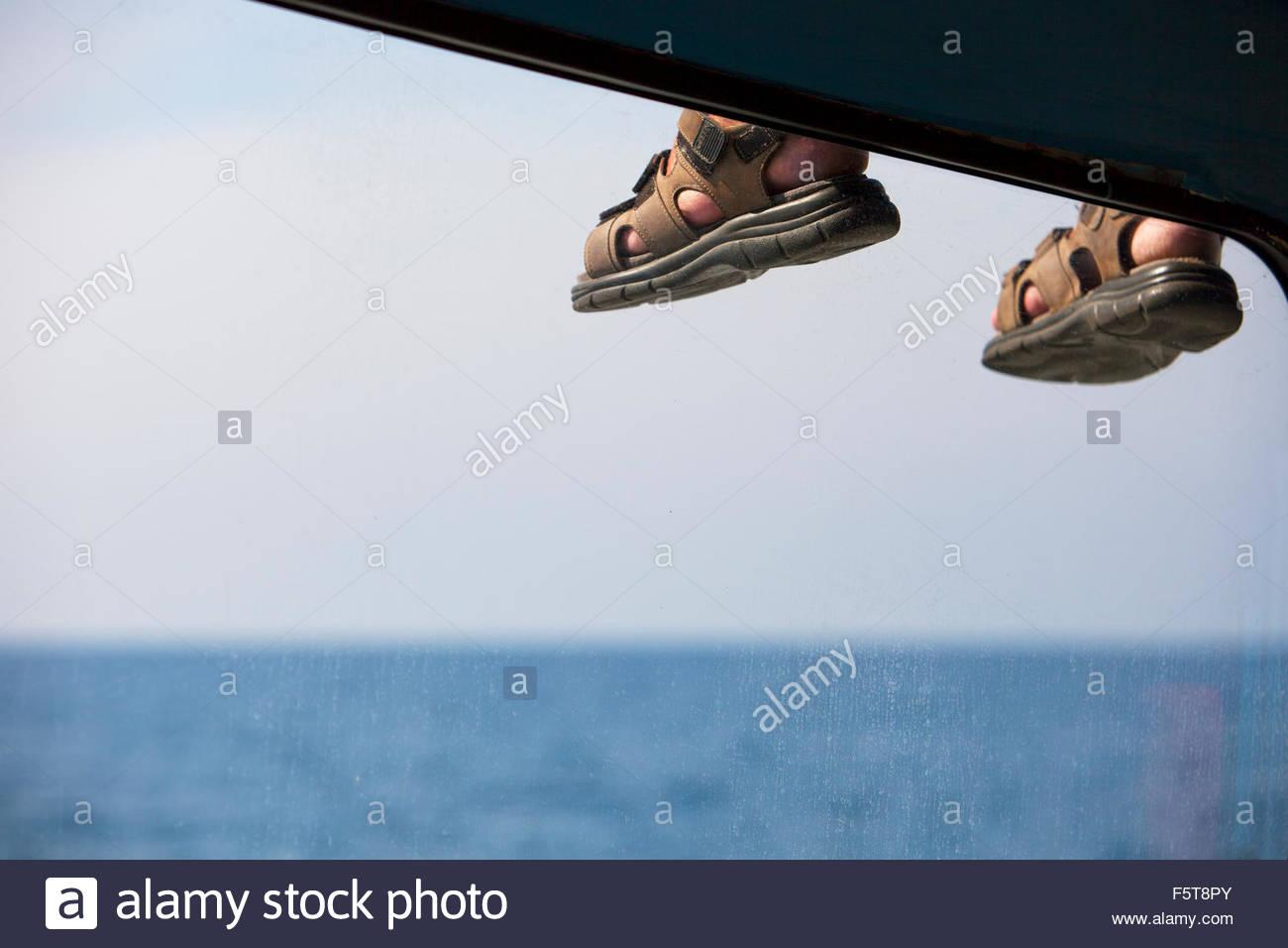 Thailand, Phuket, Thaimaa, Feet of person sitting on roof of vehicle - Stock Image