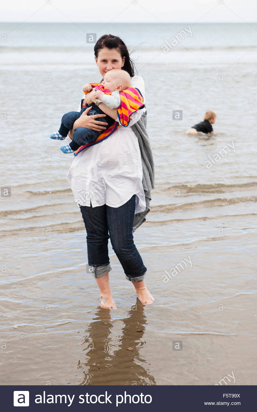 New Zealand, Auckland, Orewa, Portrait of mother with sons (2-3, 2-5 months) on beach - Stock Image