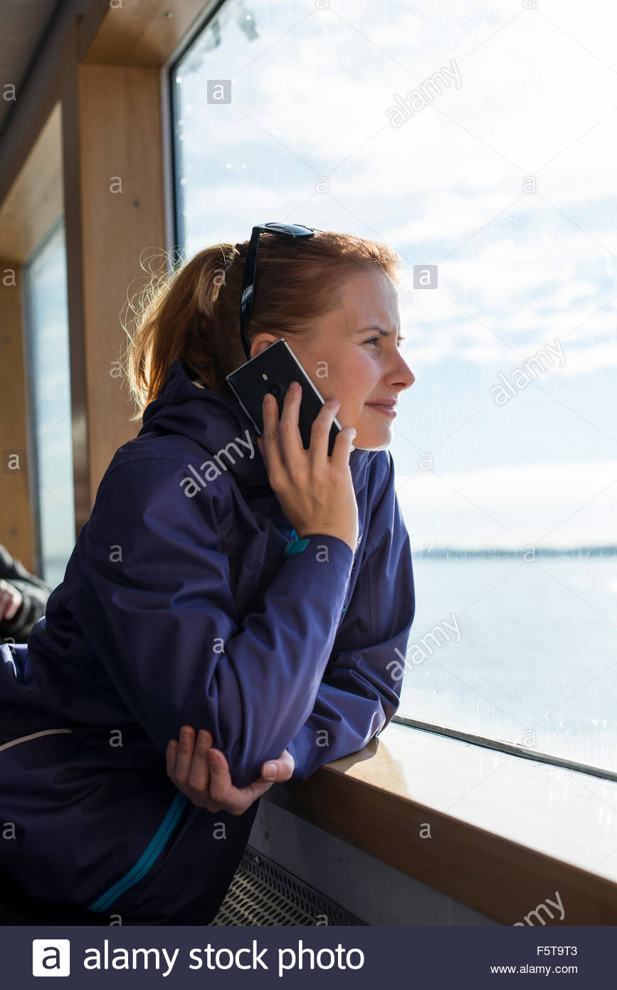 Finland, Uusimaa, Woman on ferry, looking through window - Stock Image