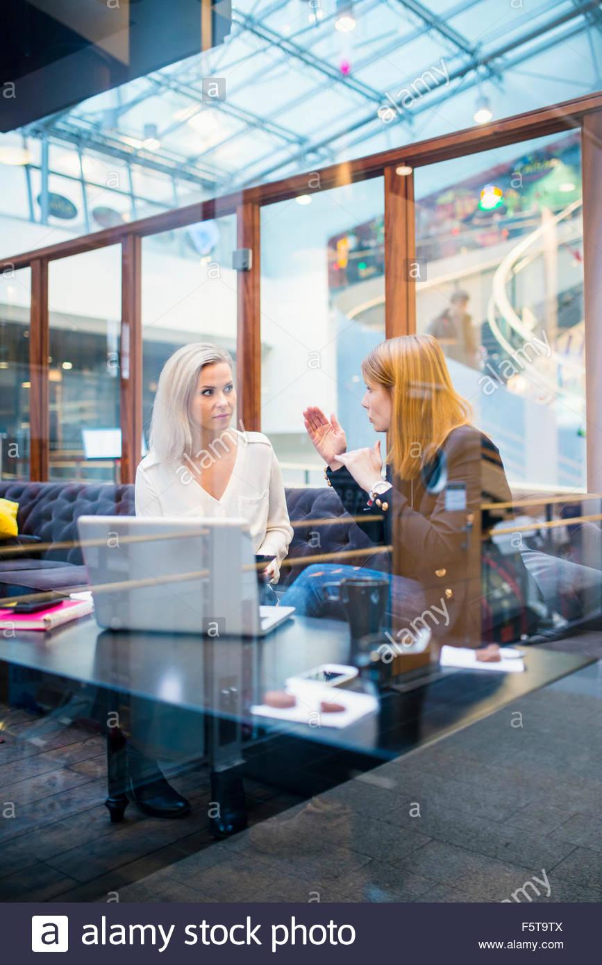 Finland, Two women talking in office - Stock Image