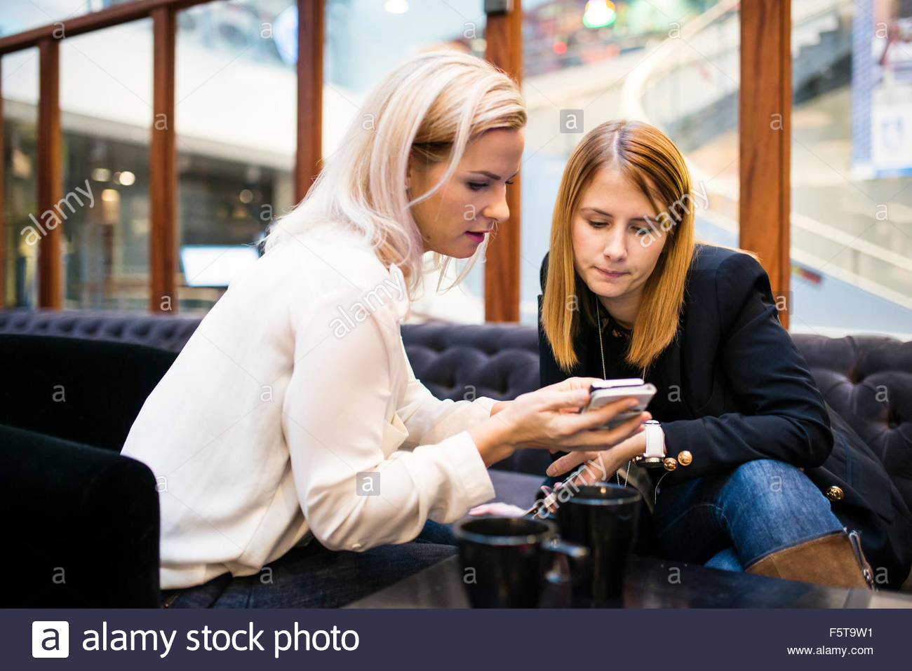 Finland, Two women looking at smartphone in office - Stock Image