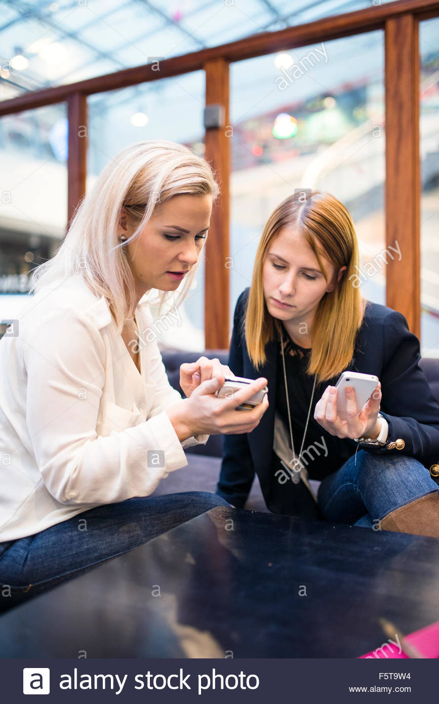 Finland, Two women looking at smartphones in office - Stock Image