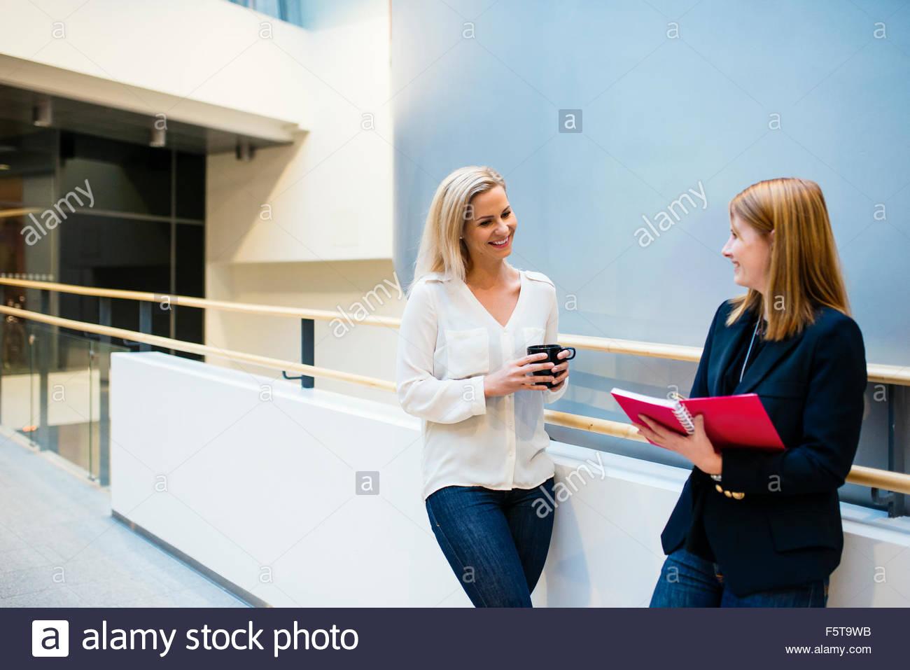 Finland, Two women talking in office corridor - Stock Image