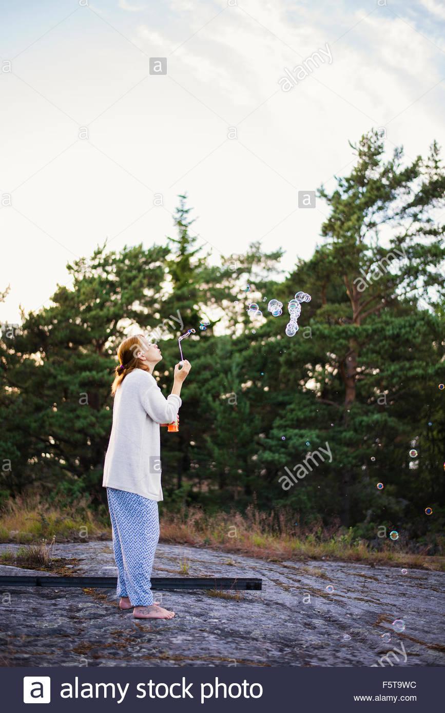 Finland, Varsinais-Suomi, Turku Archipelago, Woman playing with bubble wand - Stock Image
