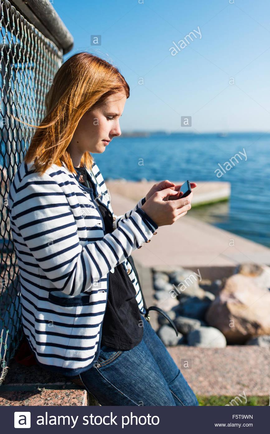 Finland, Uusimaa, Helsinki, Woman texting on mobile phone at seaside - Stock Image