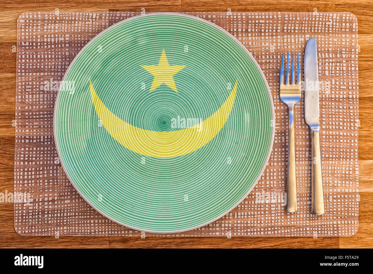 Dinner plate with the flag of Mauritania on it for your international food and drink concepts. - Stock Image