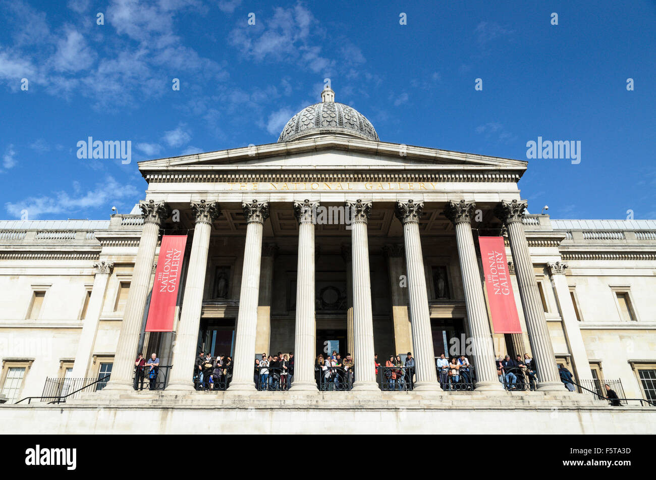 Tourists crowd the balcony of The National Gallery, Trafalgar Square, London, England, UK. - Stock Image