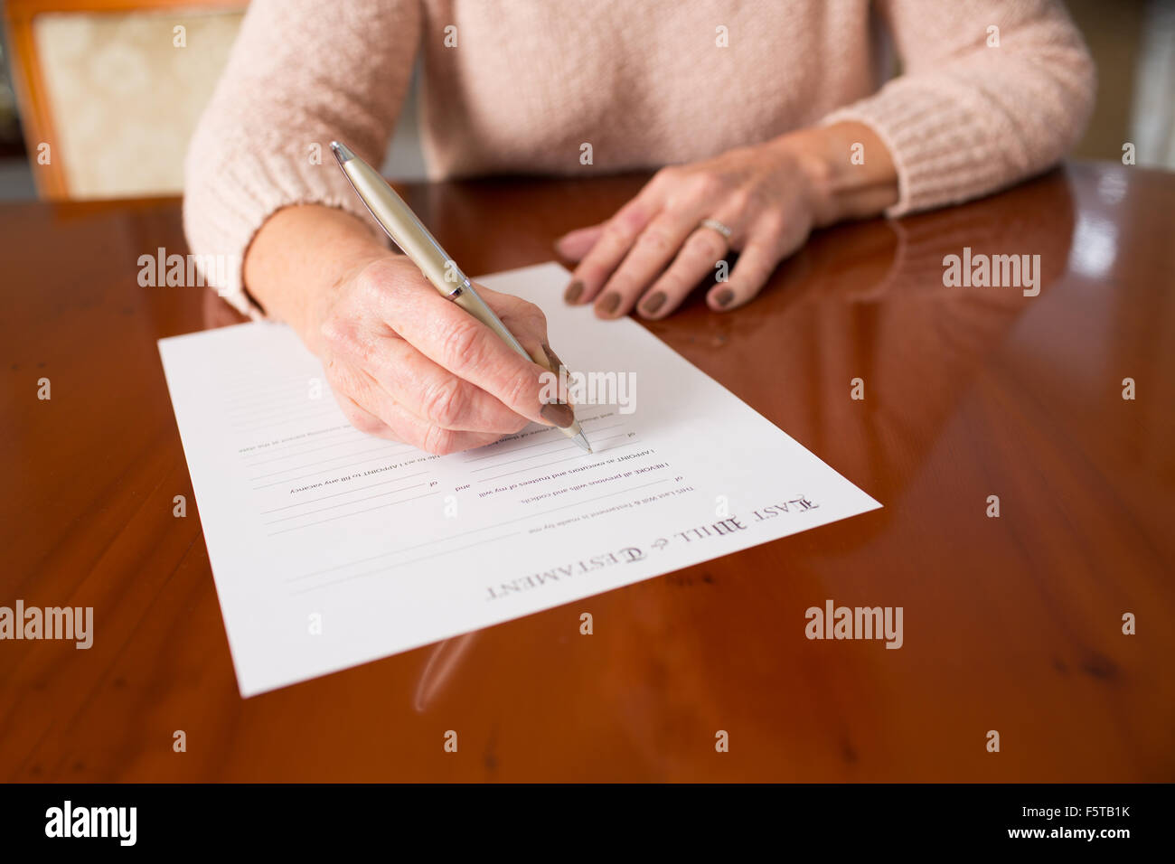 Senior Woman Signing Last Will And Testament At Home - Stock Image