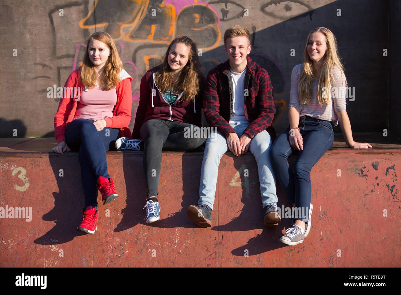Portrait Of Teenage Friends Sitting In Skateboard Park - Stock Image