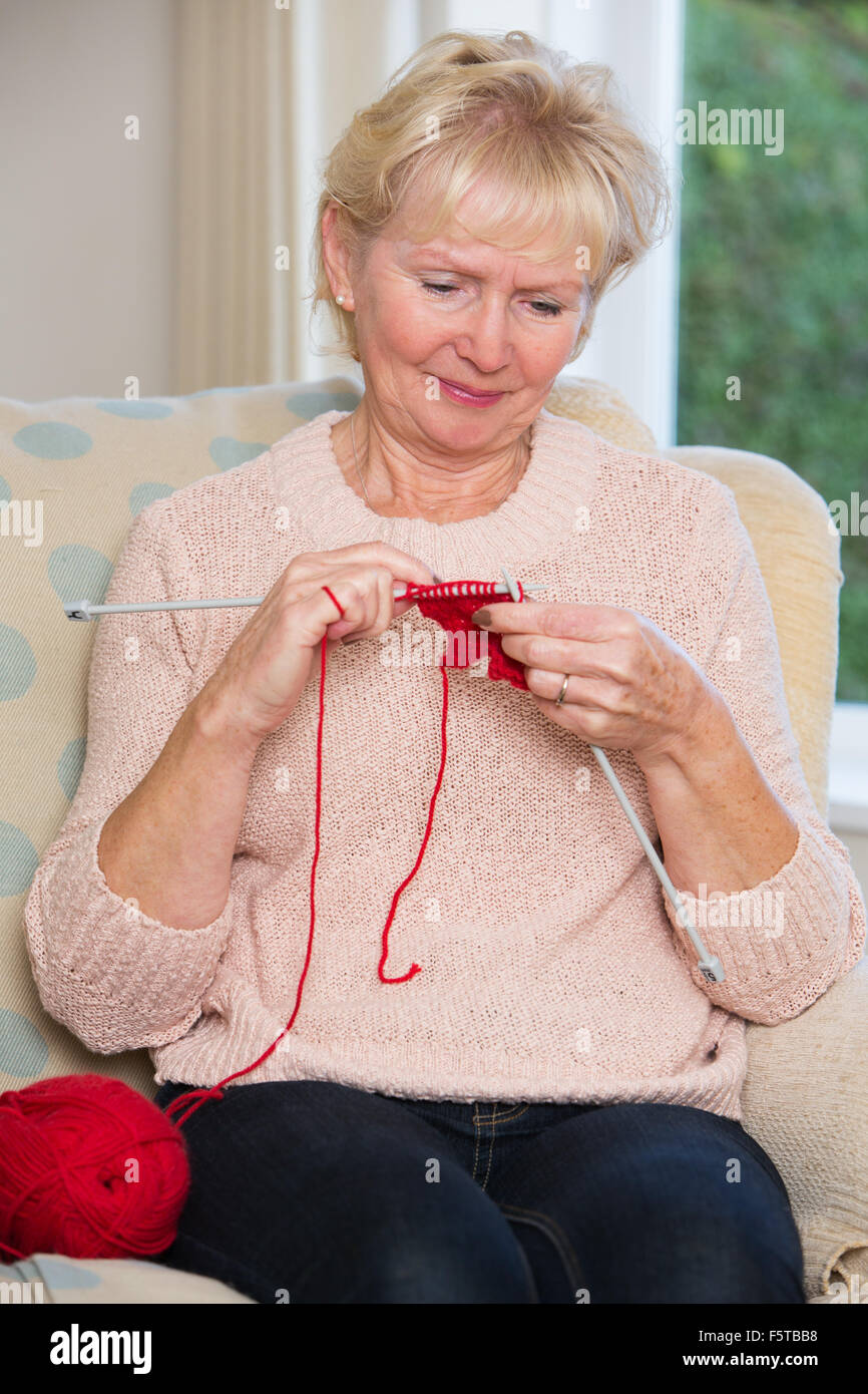 Senior Woman Sitting In Chair Knitting - Stock Image