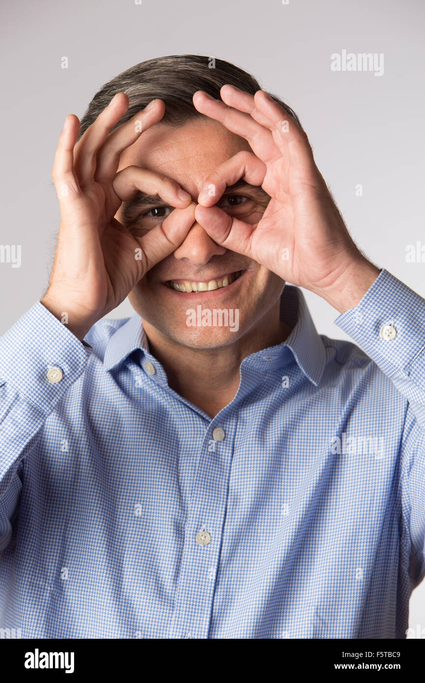 Studio Shot Of Man Making Spectacle Shape With His Hands - Stock Image